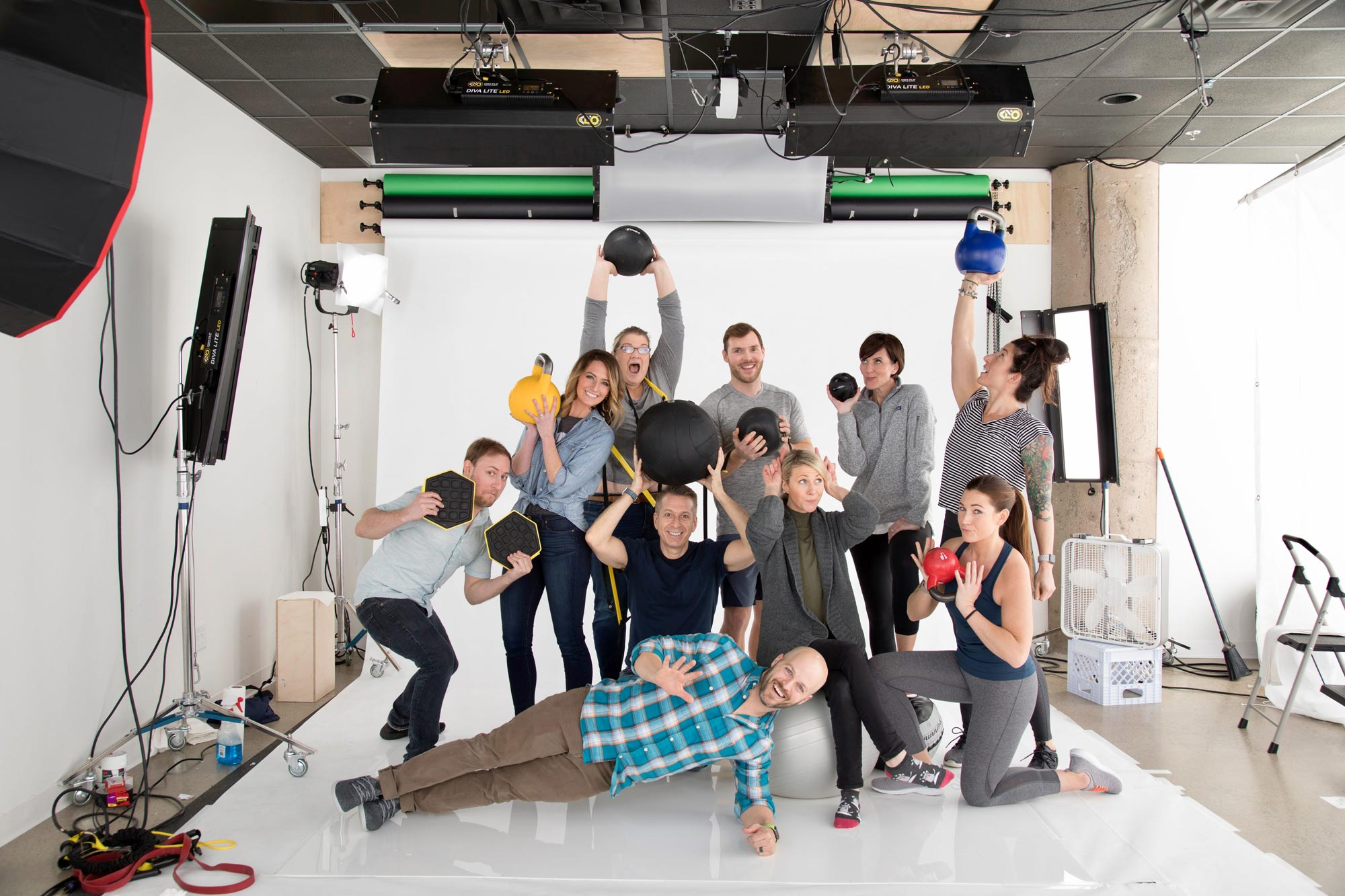 group photo on white backdrop holding workout equipment
